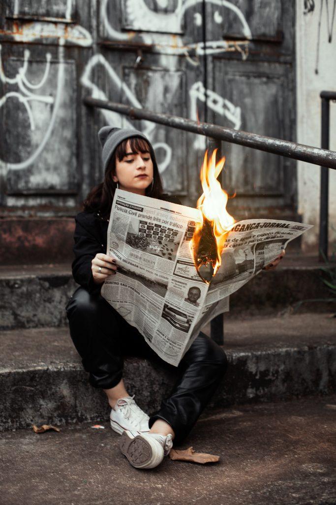 image of woman holding burning newspaper